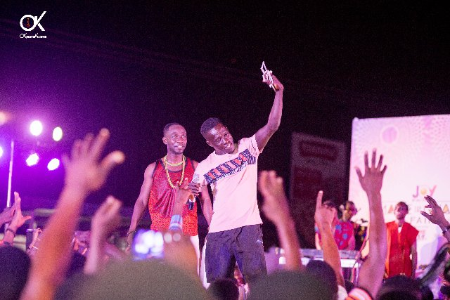 Okyeame Kwame gifts gold chain to fan at Joy Prime Made in Ghana Fair